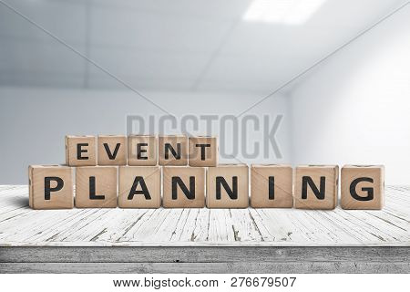 Event Planning Sign On A Wooden Desk In An Office With A Blurry Grey Background