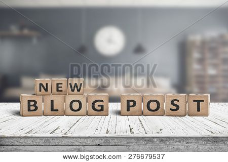 New Blog Post Sign On A Wooden Desk With A Stylish Living Room On A Blurry Background