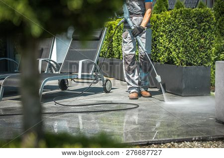 Caucasian Men In His 30s House Patio Water Cleaning Using Pressure Washer.