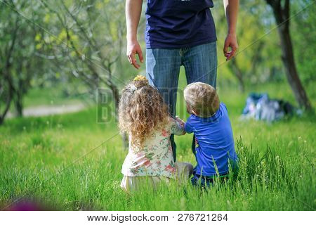 The Children Grabbed My Father's Legs. Father Plays With Children On The Street. Father's Involvemen