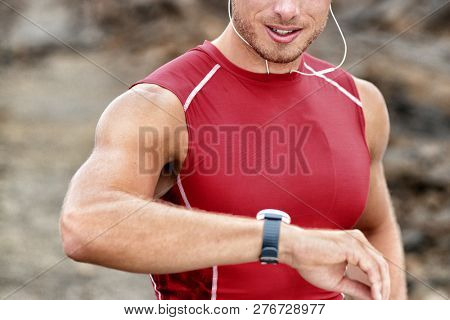 Smartwatch man athlete runner checking his wearable device tech smart watch during outdoor training - intense cardio workout exercise.