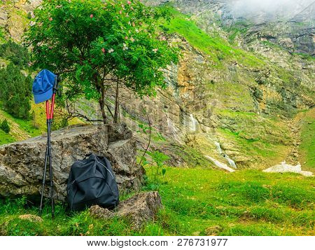 Outfit Hiker. Backpacks, Walking Sticks And A Tourist's Cap In The Mountains On A Halt Under A Tree.