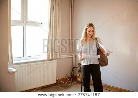 Female First Time Buyer Looking At House Survey In Room To Be Renovated