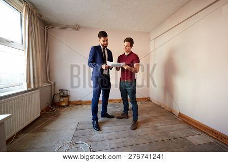 Male First Time Buyer Looking At House Survey With Realtor