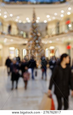 Christmas Shopping: Blurred Scene With Pedestrians Carrying Shopping Bags In Shopping Mall