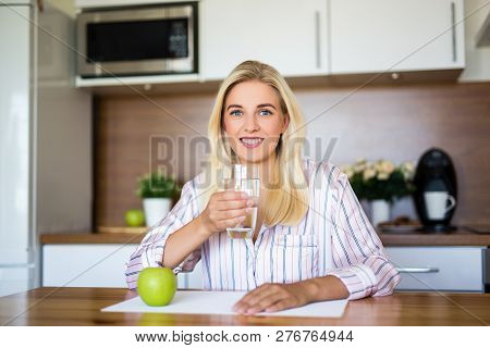 Portrait Of Young Beautiful Girl Sitting With Apple And Glass Of Water In Kitchen