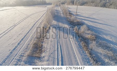 Aerial View Winter Landscape Countryside Road Through Winter Field With Forest. Winter Forest On A S