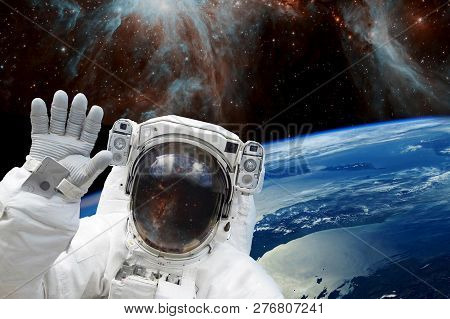 Astronaut In Outer Space In Spacesuit Against The Background Of The Earths Blue Orbit And Space With