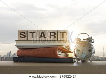 Wooden Blocks With The Word Start, Notebook, Books And Clock On Table With Panoramic City Skyline Ba