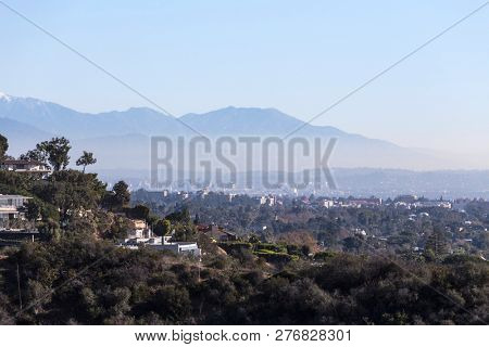 Smoggy morning cityscape view of hillside homes with Hollywood, Los Angeles and the San Gabriel Mountains in background.