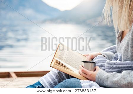 Girl Is Reading Book On Wooden Pier By Winter Sea, Mountains, Beach. Cozy Picnic With Hot Steamy Bev