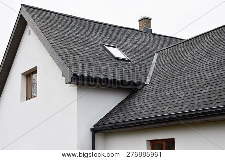 Part Of White House With New Wooden Eaves, Plastic Rain Gutter, Window And Chimney In Grey Shingles
