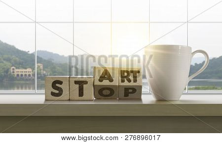 Wooden Blocks With The Word Start-stop And Coffee On Table With Panoramic Lake Landscape Background