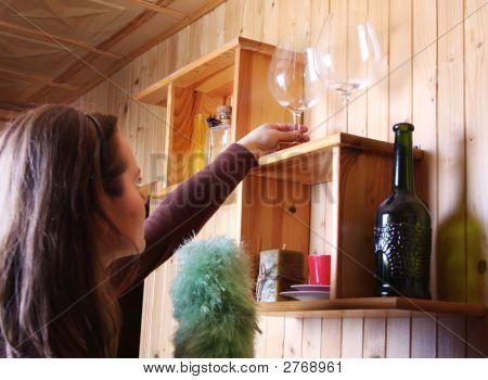Woman Is Dusting On Shelf