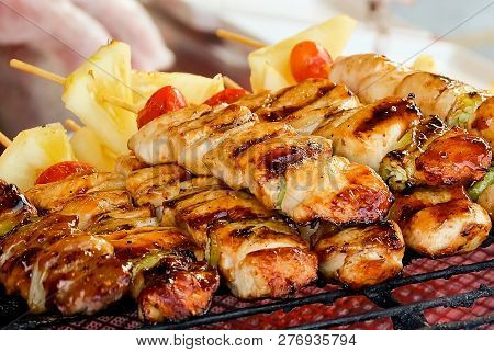 Traditional Grilled Pork And Chicken Meat Barbecue With Tomatoes And Pineapple On The Grill. One Of