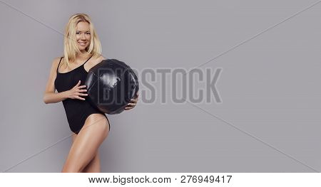 Young Happy Fitness Blonde Girl With Sporty Body Posing At Studio With Fitness Ball. Beautiful Fit G