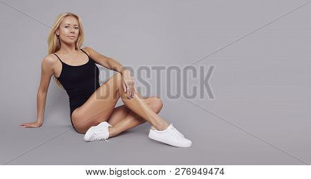 Young Fitness Blonde Girl With Sporty Body Posing At Studio. Beautiful Fit Girl. Fitness Model In Bl