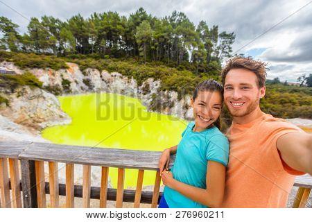 New Zealand tourist attraction couple tourists taking selfie travel destination, Waiotapu. Active geothermal green pond, Rotorua, north island.