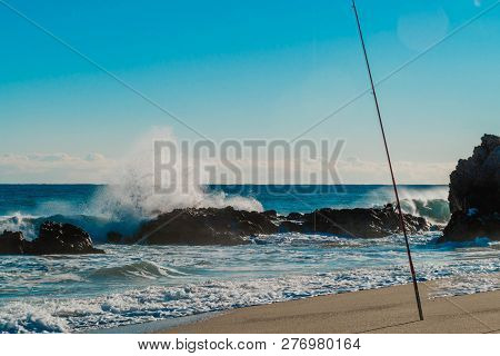 Fishing pole stuck in sand in front of waves crashing violently into boulders on sunny winter morning. poster