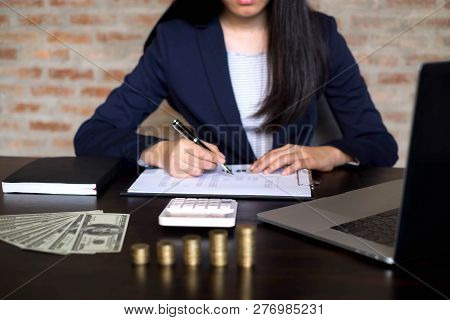Businesswoman Working With Income Statement Document On The Wood Table.business Concept.