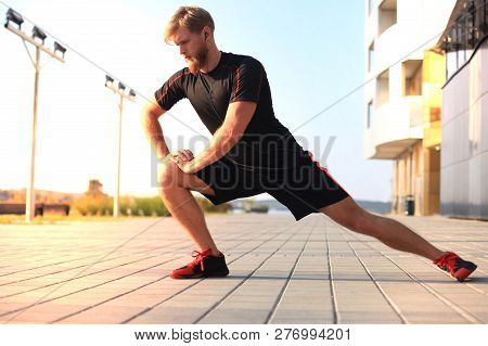 Handsome Young Man Doing Stretching Exercises Before Running While Standing Outdoors.