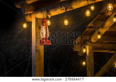 Red Metal Storm Lantern Hung Outside Rustic Log Cabin.