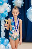 Little gymnast with her sports awards on the carpet in rhythmic gymnastics poster
