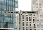 big road signs with street name of Potsdamer Strasse and Platz that means PotsDam street and square in Berlin in Germany and many modern skyscrapers in background poster