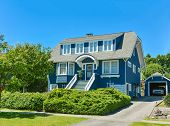 Big North American family house with detached garage in suburbs of Vancouver. A house on blue sky background poster