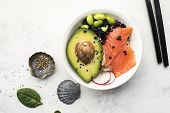 Fresh seafood recipe. Shrimp salmon poke bowl with fresh prawn, brown rice, cucumber, pickled sweet onion, radish, soy beans edamame portioned with black and white sesame. Food concept poke bowl. poster