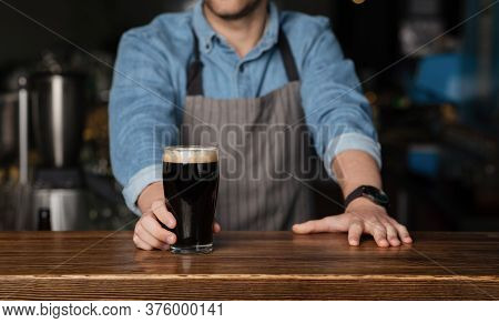 Customer Service During Party. Barman In Denim Shirt And Apron Stands Behind Wooden Counter And Give