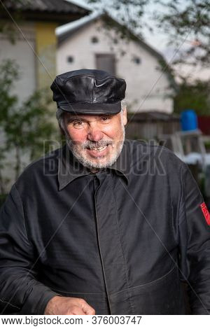 Cheerful Elderly Man With Black Old-fashioned Old Clothes And A Leather Cap Smiles And Speaks To The