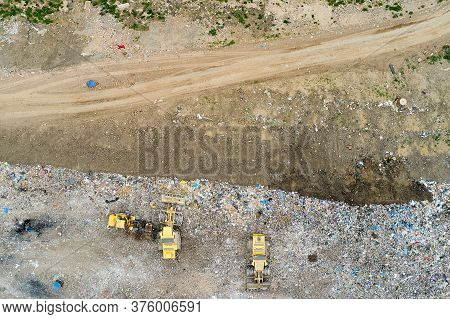 Garbage Pile In Trash Dump Or Landfill. Dump Trucks And Excavators Unloading Waste.