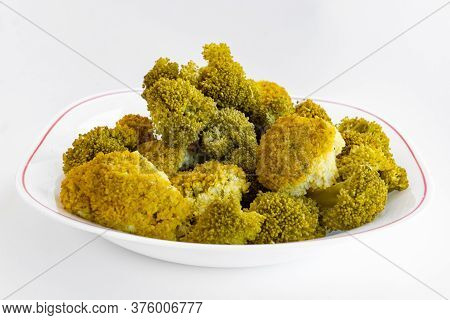 Boiled Yellowed Broccoli On A White Plate. Inflorescence Boiled Broccoli. Close-up View