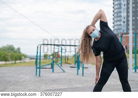 Overweight Young Woman In A Protective Mask Is Training On The Sports Ground. An Obese Girl Does Slo