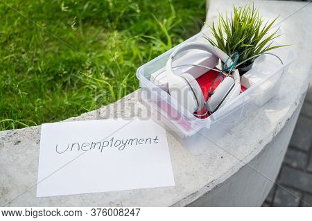 A Box Of Personal Items From The Desktop Of An Office Employee And An Unemployment Sign. Unemploymen