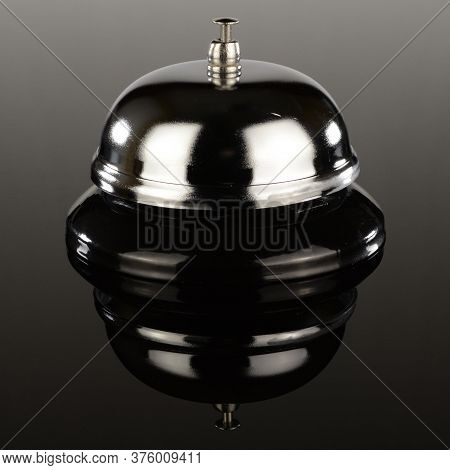 A Standard Desktop Call Bell Over A Gradient Reflective Surface.