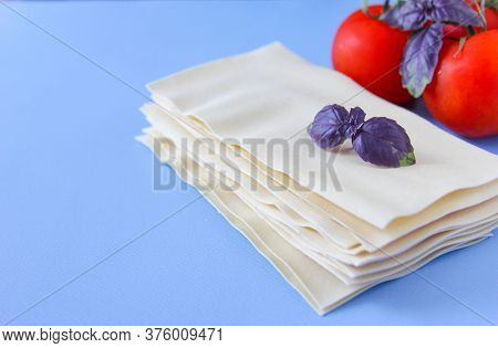 Lasagne Sheets Pasta With Tomato And Basil Leafs On A Blue Background. Ingredients For An Italian Re