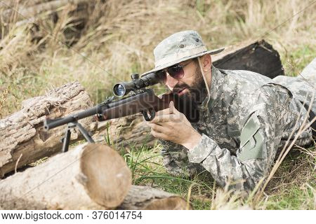 The Soldier Or Hunter In Military Uniform Is Lying Down, Hiding, Aiming And Shooting A Weapon With S