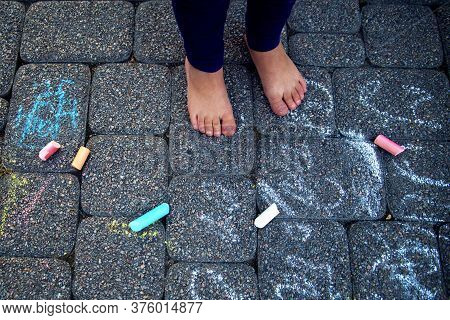 The Child Paints Chalk On The Path. Child Draws Patterns On Asphalt. Square Chalk Of Different Sizes