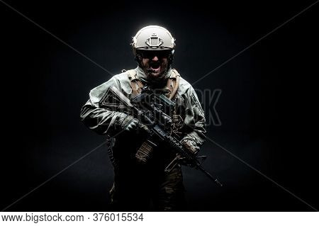 Angry Soldier In Military Equipment With A Rifle Runs Forward And Screams At Night, A Commando In Un