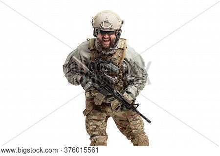 Angry Soldier In Military Equipment With A Gun Screaming On A White Background, A Commando In Unifor
