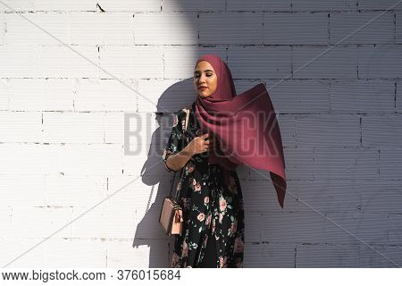 Beautiful Muslim Girl Wearing Hiyab Over A White Wall Outdoors. Lifestyle Concept.