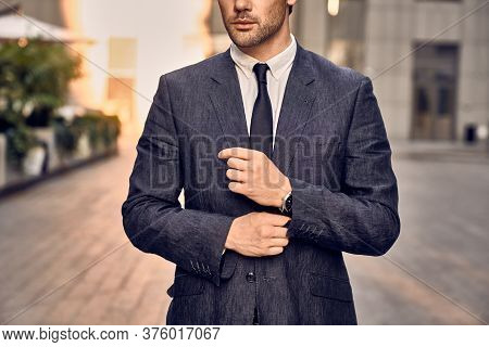 Modern Businessman. Confident Young Man In Full Suit Adjusting His Sleeve And Looking Away While Sta