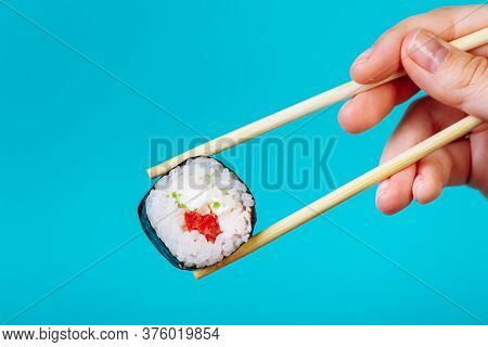 Tasty Sushi Roll Maki With Wooden Chopsticks On Blue Background Close Up. Place For Caption And Text