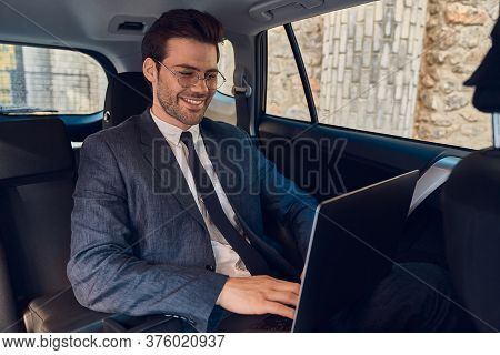 Great Solutions Every Day. Confident Young Businessman Working On His Laptop And Looking At Camera W