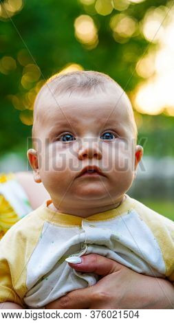 Little Baby Newborn On Arms Of Mother Watching Carefully Outdoors