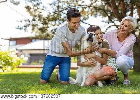Mother and her sons playing with their dog in the garden