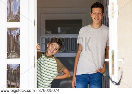 Two brothers standing in doorway of their house