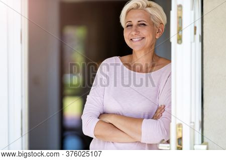 Smiling woman standing in doorway of her house